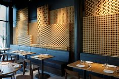 The various patterns and depths in the wood lattice wall give an added layer of dimension and textural appeal to the space while also complimenting the scale of the space by making some panels extend higher than others.