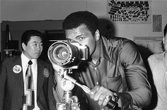 "World heavyweight boxing champion Muhammad Ali ""Cassius Clay"" sights through a camera with a zoom lens at a camera factory in Tokyo on Tuesday, June 22, 1976. The champ skipped training and instead went out for sightseeing tour aboard a chartered bus on Tuesday. (AP Photo/Nick Ut)"