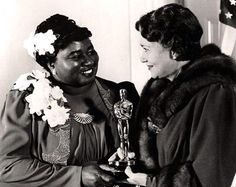"""Hattie McDaniel and an unknown woman at the Academy Awards on February 29, 1940. None of the 'Gone With The Wind' black actors were allowed to attend the film's Atlanta premiere. Hattie McDaniel, who played Mammy, won an Supporting Actress Oscar for her performance. It is reported she sat at a segregated table in the back of the venue before and after her acceptance, and that her speech (which contains a cringe-worthy reference to being """"a credit to her race"""") was written by the studio."""