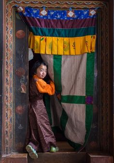 """""""Girl at the door"""". I found this girl in a monastery in Jakar, posing at the door of the main entrance to the chapel. (Photo and caption by Juan Abal Lopez/National Geographic Traveler Photo Contest) National Geographic Photography, National Geographic Travel, Bhutan, Photographs Of People, Travel Magazines, World Of Color, Culture Travel, People Around The World, Photo Contest"""