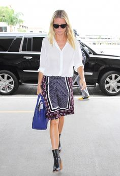 Gwyneth Paltrow weras a white blouse tucked into patterned pajama bottoms, black stacked heel booties, sunglasses and light blue structured bag.