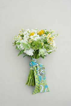 Overflowing with fever few, craspedia, snow on the mountain, queens anne's lace and white stock (which smells amazing) . Wrapped in a Vera Bradley sash that not only is a striking handle for the bouquet, but it can also double as a gift for your bridesmaids. They are going to think about you and your wedding each time they wear it. Photographed by Suzy Clement.