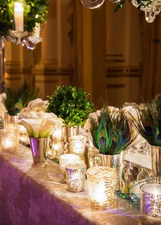 Peacock feathers, calla lilies, shimmer candles and lush of greens, the details on the this table is incredibly beautiful.