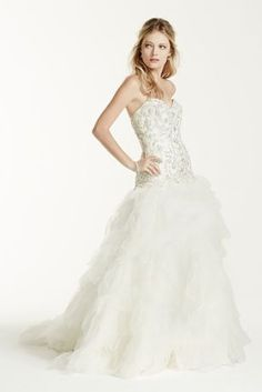 This ruffled skirt ball gown takes bridal glamour and sophistication to the next level!  Strapless sweetheart bodice features delicate beaded lace detail.  Lace-up back shapes a flattering silhouette while ensuring the perfect fit.  Eye-catching and dramatic ruffled skirt adds dimension and finishes of the look.  Chapel train. Fully lined. Lace-up back. Imported polyester. Dry clean.