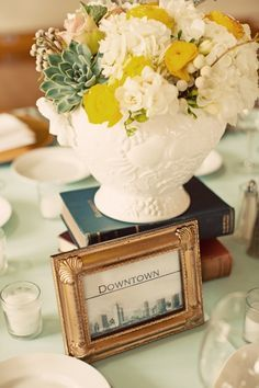 Half of the arrangements on family style tables will be elevated on vintage books provided by the bride