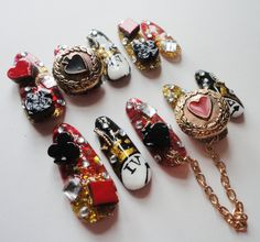 Alice in Wonderland nails!    Red, gold and black glitter bases, decorated with playing card symbols, rhinestones, a chain and hand-drawn pocket