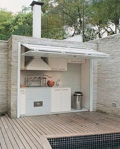 Cozy outdoor kitchen by the pool...maybe a pizza oven under there as well. I'm not liking the white though, perhaps a wood color with some stained glass?