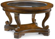 Deschanel Round Cocktail Table  This round cocktail table features an artfully inlaid compass rose design in its base. Made of cherry with a warm golden finish, the piece is accented with brass fittings and a beveled glass top, and is a great place to put up your feet and relax.