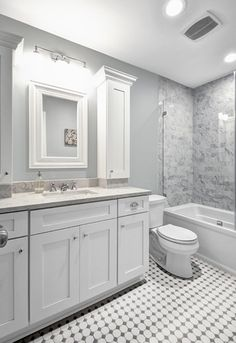 """Moving a wall 18"""" and pulling the toilet away from the door allowed this couple to expand and enhance their master bath in soothing shades of gray. Lovely."""