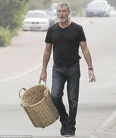 Pierce Brosnan in a casual ensemble as he collects firewood in ...