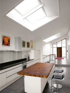 Large VELUX roof windows illuminate this stylish open-plan kitchen. Daylight streams onto the kitchen's main work area to provide the perfect light for cooking – and the warm natural light complements the home's sleek, modern interior. All this means the open-plan kitchen is not just integrated into the rest of the house, but you also have a view to the sky.