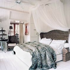 plush slate gray fur blanket adds a touch of glamour to the very natural and neutral master bedroom...texture of the fur and wicker headboard adds dimension to the all white palette.