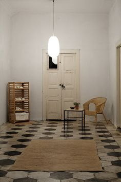 piso de cimento queimado com alguns ladrilhos em preto e branco. barrado de azuleijo rococó em toda a extensão da pia,paredes em cinza cimento rustic e armarios brancos ,um ou outro amarelo