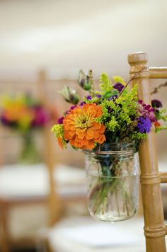 Okay, this is so cute. I want mason jars on the outside of the chairs on the inside of the aisle - with my own flowers of course!