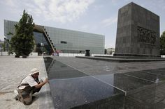 Photo Credit: Czarek Sokolowski/APA worker polishes a recently restored monument to the fighters of the Warsaw Ghetto Uprising, which stands across from the nearly finished Museum of the History of Polish Jews in Warsaw, on July 4, 2012.