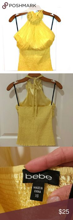 Bebe Yellow Halter Light, bright yellow chiffon halter top with 3 flowers at the neckline. Ties from the back. Elastic waist. Beautiful piece. Size XS bebe Tops Blouses