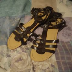 Gladiator Sandals Dark brown sandals with brass colored hardware. The sole is light tan. There are two buckles at the ankle. There is some fraying around the straps and the edge of the sole, but it isn't really noticeable. This is reflected in the price. Old Navy Shoes Sandals