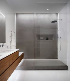 In the bathroom, solid walnut millwork is paired with raw concrete panels and white porcelain tiles.