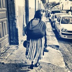Mexican lady using rebozo sling: various uses: carrying child, market goods, or simply as a wrap to keep warm