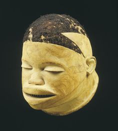 A Makonde helmet mask Mozambique/Tanzania, carved of light wood with fine incised scarification. The coiffure composed of human hair in an abstracted geometric pattern. height 8 3/4in