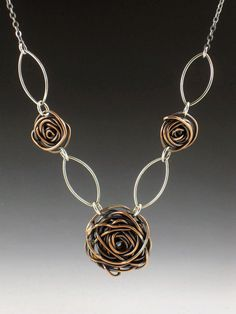 This necklace is handcrafted from sterling silver and copper wire that has been formed, soldered and oxidized. Each of the roses is formed by