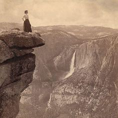 Women at cliff's edge with a waterfall in the distance. Yosemite Valley, California, 1902.