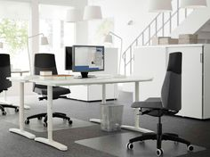 An open office with two white height adjustable desks in front of each other and swivel chairs with grey cover