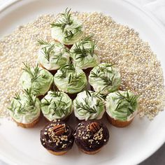 Beat almond extract into Butter Frosting; tint half of the frosting green with green and brown food coloring. Generously frost 10 of the cupcakes with white and green frosting, swirling frostings together. Top with rosemary sprigs. Set aside.