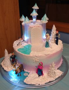 Frozen - Frozen themed cake, I got the Idea from meemawof10 to use clear pillars I all ready have and never use, this was for my niece, she loved it!  The cake is iced with pastry pride I used a daisy cutter to make the trees and piped the snowflake with white chocolate.