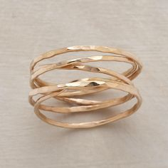 "QUINTET RING -- A hand-hammered quintet ring, with five strands of 14kt goldfill, encircles your finger in infinite style. Each ring is one of a kind. Made in the USA. Whole sizes 5 to 9. 1/4""W."
