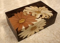 Daisy Box Daisy design flows across the top and down the sides of the box. Ripple sycamore and pear wood on burr walnut background. Size: width 240 x depth 150 x height 80mm