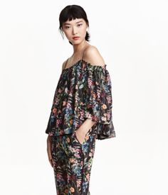 Wide-cut, off-the-shoulder blouse in crêped chiffon with glittery threads and a printed pattern. Smocking at upper edge, narrow adjustable shoulder straps, and short, double-layer sleeves with ties at top. Chiffon lining.