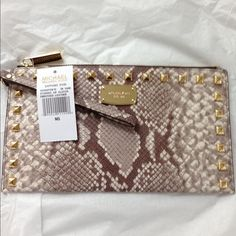 SALE   HP NWT MK leather clutch Embossed leather Michael Kors zipper large clutch/wristlet. Has 6 card slots, interior pocket large enough for iPhone 6. Measures 10 inches by 5 1/2 inches. Brand new with tags and care instructions. Beautiful snakeskin design, with golden stud embellishments. ❎NO OTHER DISCOUNTS APPLY ❎ PRICE IS FIRM. Michael Kors Bags Clutches & Wristlets