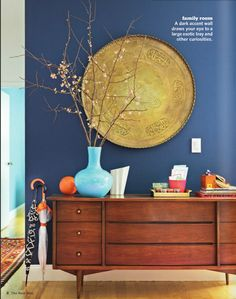 gold plate on the dark blue wall and mid century dresser - inspiration for re-staining dresser against dark blue in bedroom.  Bring in gold.