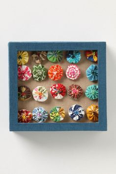 Pinwheel Push Pins -  Anthropologie.com  these are made over a large headed thumbtack - just poke it through the fabric before you pull up the yo-yo thread to enclose it.  Love the beaded embellishments.