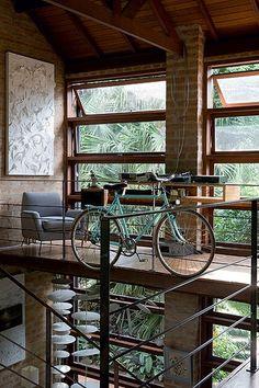 """No mezanino, a arquiteta Kita Flórido criou uma """"cabine do DJ"""" para o marido, Val Oliveira, curtir suas músicas. A bicicleta de estimação dele, presente do serralheiro Paulo Bassetto, foi presa ao guarda-corpo de ferro"""