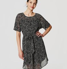 "Alluringly abstract, a tie waist perfectly balances the dolman-sleeved silhouette of this fluid chiffon covetable. Round neck. Short dolman sleeves. Removable waist tie. Shirred beneath front and back yoke. Shirttail hem. Lined with attached spaghetti strap slip. 22"" from natural waist."
