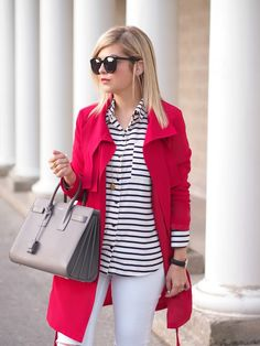 red trench + black and white stripe blouse + white pants + grey structured bag + black and gold accessories