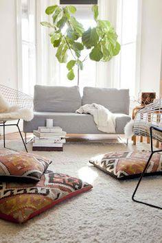 Kilim floor cushions, sheepskin & grey couch. Lovely.