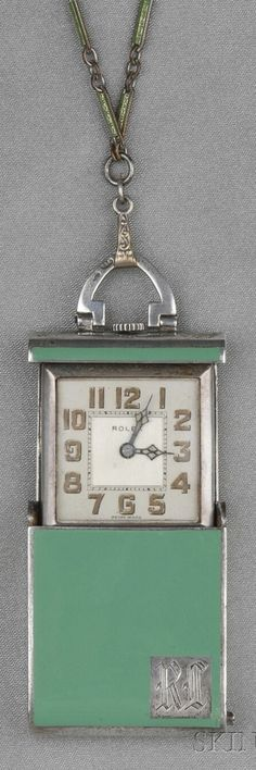 Rolex - An Art Deco Sterling Silver and Enamel Travel Watch. The green enamel case opening to reveal an ivory-tone dial with Arabic numeral indicators, enclosing 15-jewel manual-wind movement numbered, triple signed, with an associated green enamel baton-link chain, lg. 2, 24 in.