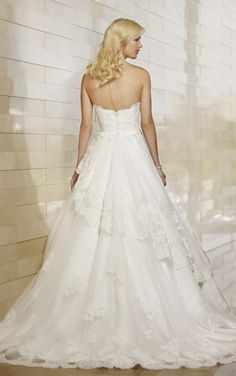 This strapless ball gown wedding dress features beautiful lace throughout. The gently pleated tiered skirt floats light as air and features ...