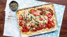 Ein Blech Blumenkohl-Pizza und ein Schälchen mit Kräutern liegen auf einem Tisch.