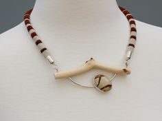 made by Linda Magi - Necklace with miniature crocheted cotton, maple twig, hand constructed argentium silver and bezel set Owyhee picture jasper. This piece is available from the Memorial Art Gallery store in Rochester, NY