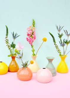 Bright Spring-colored pastel colored vases lined up in a row filled with flowers.