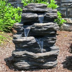 """The 24"""" Rock Waterfall Fountain With LED Lights features strategically positioned rocks to guide the water from one pool to the next, creating a natural waterfall and making it add a natural element t"""