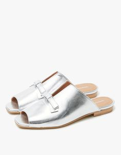 "Simple slide from Intentionally Blank in Silver. Textured leather upper. Peep toe. V-cut at top line. Vintage-inspired bow detailing. Lightly padded footbed. Low stacked heel.  • Leather upper • Leather sole • 0.25"" heel • Made in Spain"