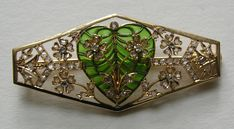 Edwardian Plique-à-jour Heart Diamond 18k Brooch.  This brooch is European origins and a green plique-à-jour heart accented with flowers set with over seventy mine cut diamonds. Measures 2 1/8ths inches by 1 inch. Unmarked. 18k. The trombone clasp is in working order. There may be an old repair to the back where the plique heart is attached to the brooch.