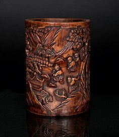 China, 18th cent. (Qing Dynasty 1644-1911). Carved bamboo. Cylindric form with a deeply carved design showing a continuous scene of boys playing under pine trees. Sign. 'Zhou Zhang Youke' H. 14,5 cm. 竹筆筒