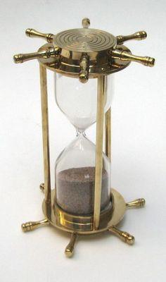 """Přesýpací hodiny * leštěná mosaz s podstavci ve taru kormidla s třemi sloupci a skleněnými baňkami s hnědým pískem časomíry na  minut, tyto hodiny vozily na lodích námořníci a proto se jím říká """"námořní""""."""