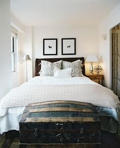 Rustic Bedroom - An aged trunk at the end of a wooden bed dressed with white linens and patterned shams